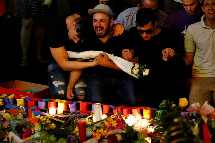A man sits and cries after taking part in a candlelight memorial service the day after a mass shooting at the Pulse gay nightclub in Orlando